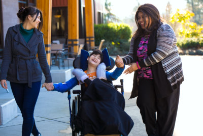 happy disabled kid with 2 women