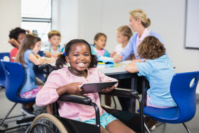 little girl on a wheelchair smiling