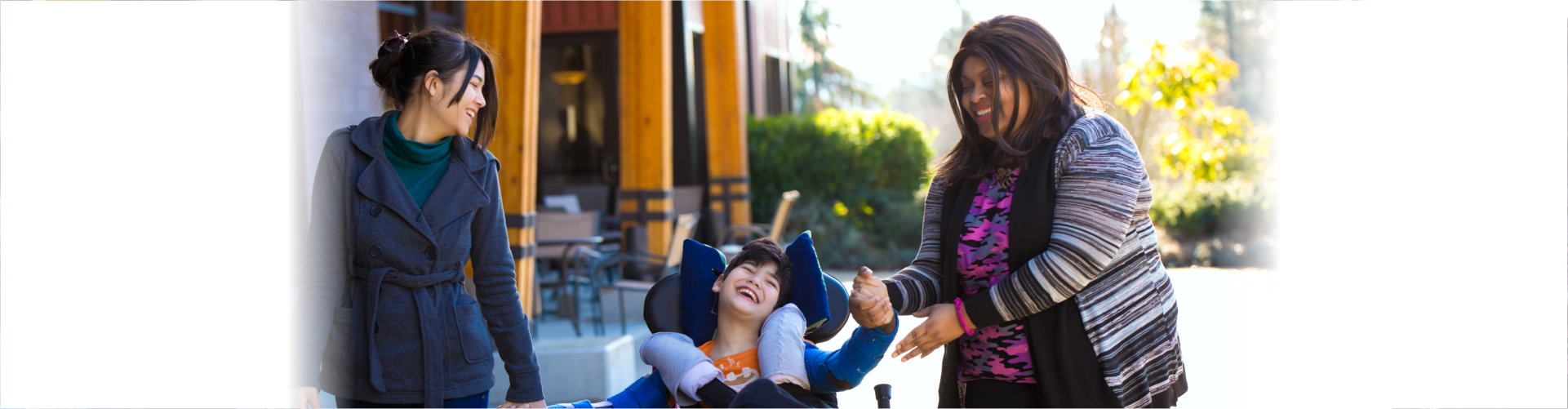 happy disabled kid with two women